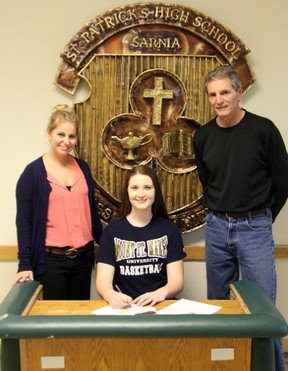 Caroline Hummel (middle) is pictured with her basketball coaches Lindsay Sharpe and Ed Dragan as she signs her National Letter of Intent to play basketball for Mount St. Mary's University. Hummel will be going to the NCAA Division 1 school on a scholarship beginning in 2014. SHAUN BISSON/ THE OBSERVER/ QMI AGENCY