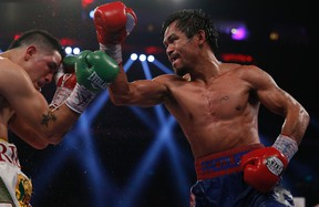 Manny Pacquiao of the Philippines fights Brandon Rios (L) of the U.S. during their World Boxing Organization (WBO) International 12-round welterweight boxing title fight at the Venetian Macao hotel in Macau November 24, 2013. REUTERS/Tyrone Siu