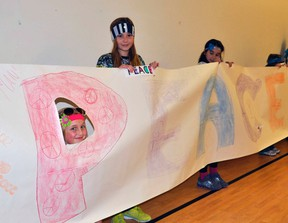 St. Columban students Hannah Nolan (left), Kimmi Doyle and Jenna Deck hold a portion of their Peace, Really banner the students' council displayed for their colleagues during an anti-bullying assembly at the school Wednesday, Nov. 27. ANDY BADER/MITCHELL ADVOCATE