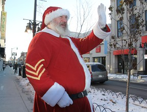 Randy Young, playing Sergeant Santa, waves to passing motorists on Princess Street Friday morning as he stops in the city on his cross-province toy drive for the children of military personnel. Michael Lea The Whig-Standard