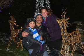 Kiara Szabo, left, of London, threw a switch that lit over 65,000 Christmas lights at a home in Port Stanley on Saturday. Szabo has leukemia and is headed to Hawaii after Christmas thanks to the Make-a-Wish Foundation of Southwestern Ontario. The Christmas display in Port Stanley is collecting donations for Make-a-Wish. Szabo is pictured with her father John and mother Roxanne. (Ben Forrest, Times-Journal)