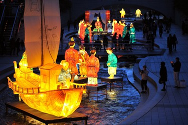 Visitors walk beside colorful lanterns ahead of the Seoul Lantern Festival at the Cheonggye stream in central Seoul on October 31, 2013. AFP PHOTO / JUNG YEON-JE