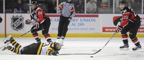 Kingston's Sam Bennett keeps his eye on the puck as he goes to the ice in front of Niagara IceDogs Aaron Haydon, left, and Zach Wilkie during the first period of Friday night's OHL game at the Rogers K-Rock Centre. (Michael Lea/The Whig-Standard)