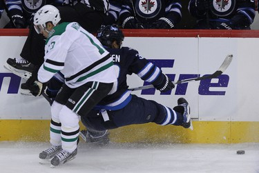 Winnipeg Jets defenceman Dustin Byfuglien loses his balance under pressure from Dallas Stars forward Ray Whitney during first-period NHL action at MTS Centre in Winnipeg, Man. on Sat., Dec. 14, 2013. Kevin King/Winnipeg Sun/QMI Agency
