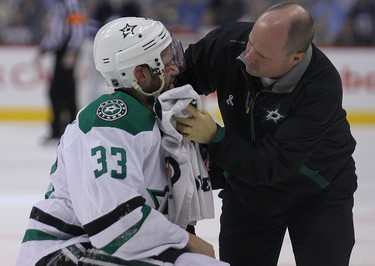 Dallas Stars defenceman Alex Goligoski is attended to by a trainer after he was hit by Winnipeg Jets forward Anthony Peluso during second-period NHL action at MTS Centre in Winnipeg, Man. on Sat., Dec. 14, 2013. Peluso was given a five-minute major for boarding and a game misconduct. Kevin King/Winnipeg Sun/QMI Agency