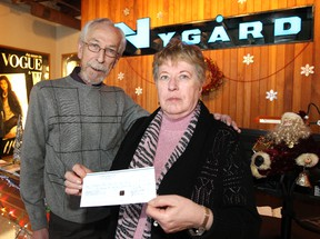 Pat Chapdelaine (left), executive vice-president of operations and technical design for Nygard International, presents a cheque to Kai Madsen, Christmas Cheer Board executive director, at the Nygard offices on Inkster Boulevard on Thu., Dec. 19, 2013. Winnipeg Sun/QMI Agency