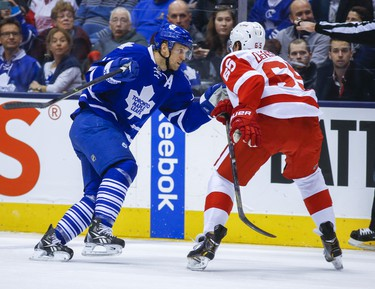 Toronto Maple Leafs' Jay McClement  and Detroit Red Wings' Danny DeKeyser during first-period action at the Air Canada Centre on December 21, 2013. (Ernest Doroszuk/Toronto Sun/QMI Agency)