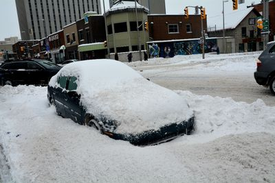 A car left on the street downtown for too long was mostly buried in snow by mid-day Sunday. (Chris Hofley/Ottawa Sun