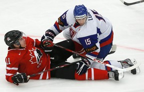 Slovakia's Mario Lunter, right, knocks down Canada's Bo Horvat during the third period of their IIHF World Junior Championship game in Malmo, Sweden, Dec, 30, 2013.