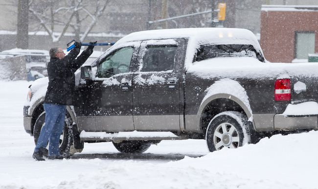 Paul Stark clears snow off his pickup truck in a York Street parking lot in London, Ontario on Monday January 6, 2014.  
