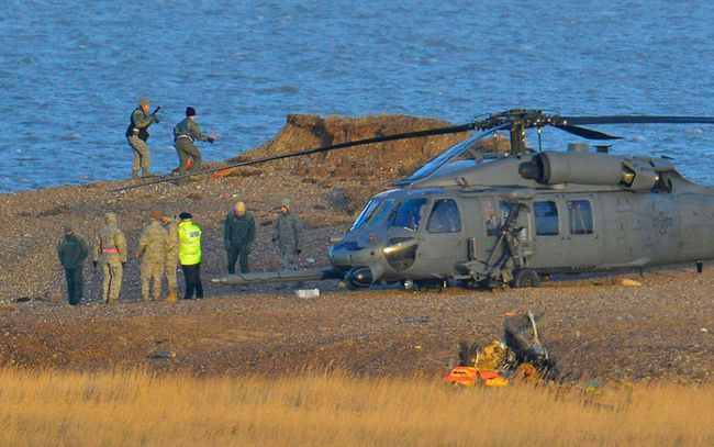 A Pave Hawk helicopter, military personnel and emergency services attend the scene of a helicopter crash on the coast near the village of Cley in Norfolk, eastern England on January 8, 2014. (REUTERS/Toby Melville)