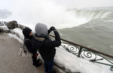 """Visitors take pictures overlooking the falls in Niagara Falls, Ontario, January 8, 2014. The frigid air and """"polar vortex"""" that affected about 240 million people in the United States and southern Canada will depart during the second half of this week, and a far-reaching January thaw will begin, according to AccuWeather.com.   REUTERS/Aaron Harris"""