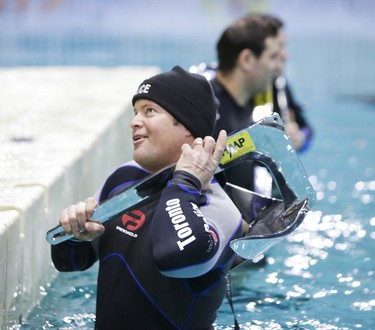 """Toronto Police Marine Unit Const. Mike Rymsha holds a 15-kilo anchor in the frigid water in a """"lake"""" set up for the Toronto International Boat Show inside the Ricoh Coliseum during the 7th annual """"Anchors Aweigh Relay"""" on Thursday, January 9, 2014. (Ernest Doroszuk/Toronto Sun)"""