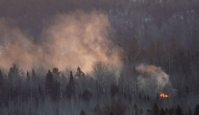 Flames and smoke are seen at the site of a train derailment in Wapske, New Brunswick, January 8, 2014. A Canadian National Railway train carrying propane and crude oil derailed and caught fire on Tuesday in northwest New Brunswick, Canada, the latest in a string of train accidents that have put the surging crude-by-rail business under heavy scrutiny. No one was injured but about 45 nearby homes were evacuated. REUTERS/Mathieu Belanger