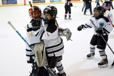 EGHA Atom B Warriors players Madeline Stoik (left) and Emma Drever celebrate with their teammates after their won their game against the Swat Bullets 2-0 during Quikcard Edmonton Minor Hockey Week play at Oliver Park Arena in Edmonton, Alta., on Sunday, Jan. 12, 2014. Ian Kucerak/Edmonton Sun/QMI Agency
