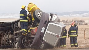 Fire crews from Pincher Creek and Lundbreck extricate the driver from a toppled semi on Highway 22, the latest victim of high winds on the notorious stretch of road. Greg Cowan photo/QMI Agency