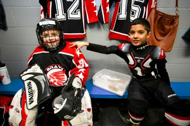 (Left to right) Goaltender Rylan Connors, 7, and forward Arjun Kaila, 7, get ready in the Brave Raiders dressing room before their team's game with the Swat Stars during Quikcard Edmonton Minor Hockey Week play at Russ Barnes Arena in Edmonton, Alta., on Monday, Jan. 13, 2014. Ian Kucerak/Edmonton Sun/QMI Agency
