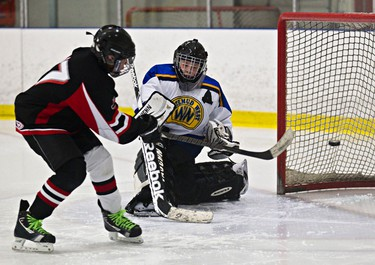 Whitemud West Thunderkings' Levi Richardson (in white) can't stop SWAT Stars' Ashwin Kaul (in black) from scoring a goal during Quikcard Edmonton Minor Hockey Week action at Mill Woods Recreation Centre in Edmonton, Alta., on Wednesday, Jan. 15, 2014. Codie McLachlan/Edmonton Sun/QMI Agency