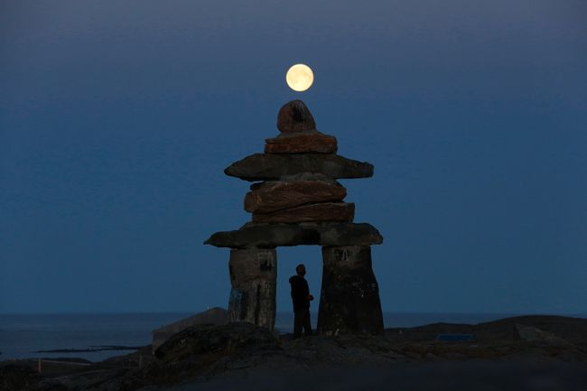 A man looks at a giant inukshuk as the moon rises above it in Rankin Inlet, Nunavut August 21, 2013.  REUTERS/Chris Wattie