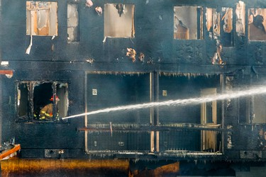 A firefighter shoots water out of a a multi-unit townhouse complex on Panatella Square NW in Calgary, Alta., on Friday January 10, 2014. Three buildings under construction were burned to the ground, a fourth was badly damaged, and 14 homes were evacuated in the overnight fire. The only injury came when a fire investigator slipped and fell on icy sidewalks later in the morning. (Lyle Aspinall/Calgary Sun/QMI Agency)