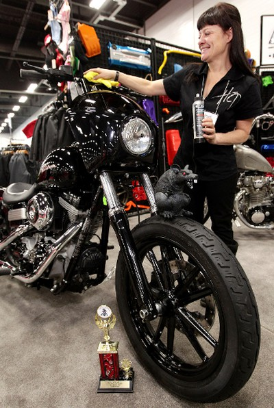 Rachele Temreck polishes a motorcycle at the After Dark Motorcycles booth during The Motorcycle and ATV Show at the Edmonton Expo Centre, in Edmonton, Alta., on Friday Jan. 17,  2014. The show runs from Jan 17 - 19. David Bloom/Edmonton Sun/QMI Agency