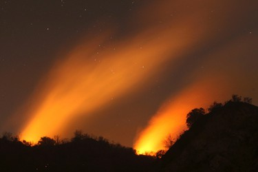 Smoke rises under a starry sky at the Colby Fire in Glendora, California, January 17, 2014. Firefighters battling a blaze sweeping across acres of dry brush for a second day in the foothills near Los Angeles kept advancing flames largely in check on Friday, helped by diminishing winds that allowed most evacuees to return home. REUTERS/David McNew