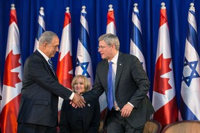 Israel's Prime Minister Benjamin Netanyahu, left, shakes hands with his Canadian counterpart Stephen Harper as Harper's wife Laureen watches during a welcoming ceremony for Harper at Netanyahu's office in Jerusalem on January 19, 2014. (REUTERS/Baz Ratner)