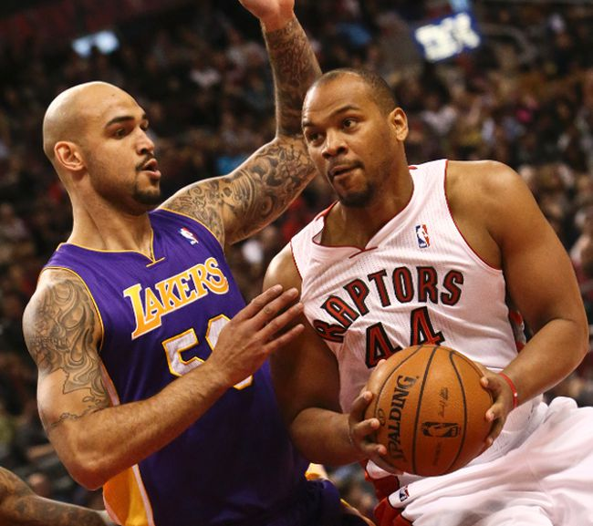 Lakers' Robert Sacre (left) defends against Raptors' Chuck Hayes on Sunday at the Air Canada Centre. (DAVE THOMAS/TORONTO SUN)
