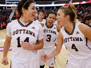 University of Ottawa GeeGee's Angela Tilk, left, Julia Soriano, center, and Charlotte MacKenzie celebrate their 57-47 win over the Carleton University Ravens during the MBNA Capital Hoops Classic basketball game at Canadian Tire Centre in Ottawa on Tuesday January 21, 2014.Darren Brown/Ottawa Sun/QMI Agency