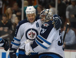 Winnipeg Jets center Olli Jokinen (12) celebrates with goalie Ondrej Pavelec (31) after the game against the Anaheim Ducks at Honda Center. The Jets defeated the Ducks 3-2. Mandatory Credit: Kirby Lee-USA TODAY Sports