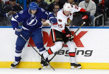 Jan 23, 2014; Tampa, FL, USA; Tampa Bay Lightning defenseman Eric Brewer (2) battles for the puck with Ottawa Senators right wing Chris Neil (25) during the second period at Tampa Bay Times Forum. Mandatory Credit: Kim Klement-USA TODAY Sports