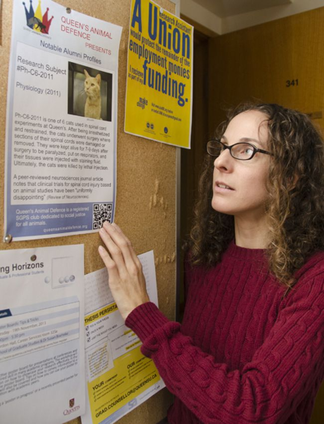 Zipporah Weisberg, strategic co-ordinator/outreach co-ordinator for the Queen's Animal Defence, looks at one of the posters from the group's recent on-campus campaign. Julia McKay The Whig-Standard