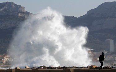 A passer-by walks as a high wave hits the waterfront in Marseille, France, March 14, 2013. (REUTERS/Jean-Paul Pelissier)