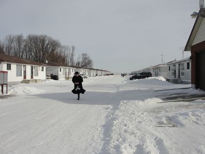 Clad in the ultra-orthodox Jewish group's traditional attire, a member of Lev Tahor scoots down a frozen laneway lined by the duplexes the group is renting near Chatham, Ont. (JANE SIMS/QMI Agency)