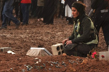 A female member of the Kurdish People's Protection Units (YPG) mourns over the grave of her fellow fighter, who was killed during clashes with the al Qaeda-affiliated Islamic State of Iraq and the Levant (ISIL), in Ras al-Ain January 28, 2014. REUTERS/Rodi Said
