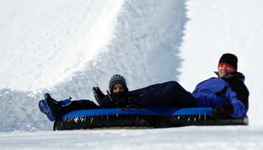 Andrew Harrington, left, and his father, Murray, enjoy a ride on innertubes during the opening day of Winterlude at Jacques Cartier Park in Gatineau, QC on Friday January 31, 2014.Darren Brown/Ottawa Sun/QMI Agency
