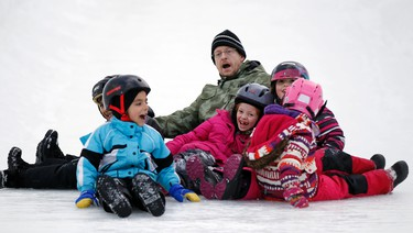 From left, St. Thomas More Catholic School students, Jack, Jessica and Lauren, race down an ice slide with parent-guardian, Michael Kenny, during the opening day of Winterlude at Jacques Cartier Park in Gatineau, QC on Friday January 31, 2014.Darren Brown/Ottawa Sun/QMI Agency