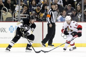 Sidney Crosby battles with Erik Karlsson during first-period action in Pittsburgh Monday night. USA TODAY