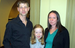 Kingston's Matt Henderson, seen here with Marissa Dunley, 8, and his girlfriend Christine Dunley, received an award from the City of Kingston Tuesday night for his actions in saving two co-workers during the blaze on Dec. 17, 2013, that destroyed a building that was being constructed at 663 Princess St. Paul Schliesmann/TheWhig-Standard/QMI Agency