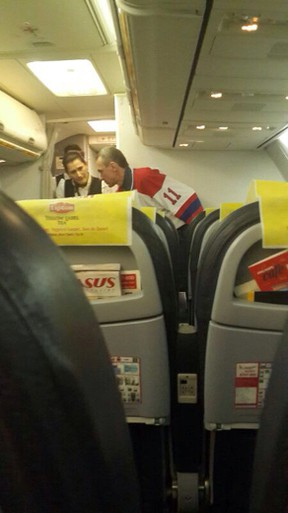 The man (R) who attempted to hijack an airliner from Ukraine is spoken to by flight attendants on February 7, 2014, after the plane was forced down in Istanbul. (AFP PHOTO/CIHAN NEWS AGENCY)