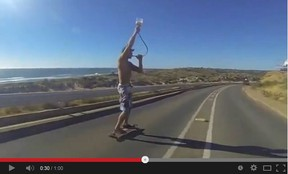 A skateboarder funnels beer as he cruises down a road. The drinking game has gone viral.