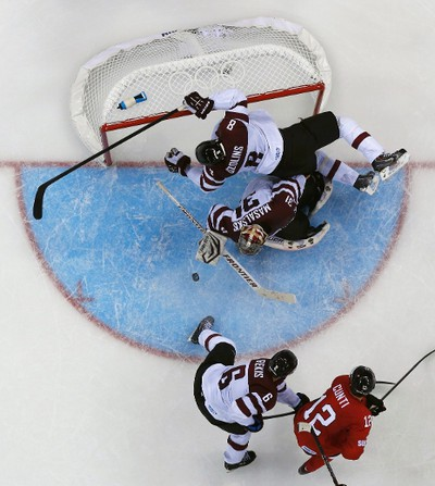Latvia's Sandis Ozolins (8) knocks the net off the posts as teammate goalie Edgars Masalskis (C) makes a save in front of Switzerland's Luca Cunti (bottom, R) and Latvia's Arvids Rekis, during the third period of their men's preliminary round hockey game at the Sochi 2014 Winter Olympic Games February 12, 2014. REUTERS/Brian Snyder (RUSSIA  - Tags: SPORT ICE HOCKEY OLYMPICS)