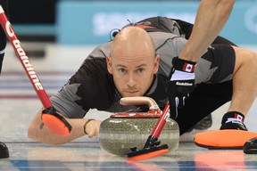 Canada's Ryan Fry throws a stone during a men's curling round robin session at the Ice Cube Curling Center during the Sochi Winter Olympics on February 14, 2014.  (AFP PHOTO / DAMIEN MEYER)