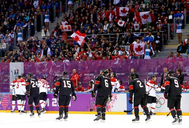 Flags wave as fans celebrate a goal by Canada's Shea Weber against Austria during their men's preliminary round ice hockey game at the 2014 Sochi Winter Olympics, February 14, 2014. REUTERS/Gary Hershorn