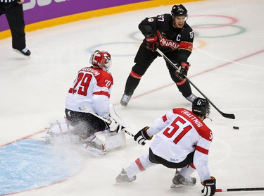 Canada's Sidney Crosby (top) sets up a play that resulted in a goal by teammate Jeff Carter (not shown) against Austria's goalie Bernhard Starkbaum and Austria's Matthias Trattnig during the second period of their  men's preliminary round ice hockey game at the Sochi 2014 Sochi Winter Olympics, February 14, 2014. REUTERS/Jim Young