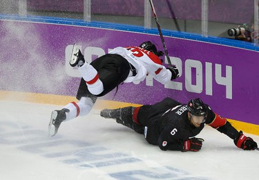 Austria's Michael Raffl flies over Canada's Shea Weber during the second period of their men's preliminary round ice hockey game at the Sochi 2014 Sochi Winter Olympics, February 14, 2014.   REUTERS/Jim Young