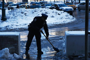 A New York Police Officer clears snow and ice on a street after a night of snow in New York, February 14, 2014. A four-day-old storm that dumped heavy snow, sleet, and freezing rain across the northern U.S. East Coast overnight should taper off as Friday wears on, forecasters said, bringing a measure of relief to winter-weary residents and travelers.REUTERS/Eduardo Munoz