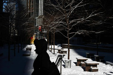 A woman walks on a street after a night of snow in New York, February 14, 2014. A four-day-old storm that dumped heavy snow, sleet, and freezing rain across the northern U.S. East Coast overnight should taper off as Friday wears on, forecasters said, bringing a measure of relief to winter-weary residents and travelers.REUTERS/Eduardo Munoz