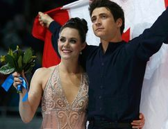 Canada's Tessa Virtue and Scott Moir wave their flag after the flower ceremony for the figure skating ice dance free dance program at the Sochi 2014 Winter Olympics, February 17, 2014. (REUTERS)