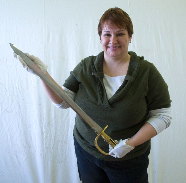 Shanna Dunlop holds a British navy cutlass, one of the artifacts on display at the War of 1812  exhibit at Fanshawe Pioneer Village. The display tries to put a human face on the war's impact. (DEREK RUTTAN, The London Free Press)